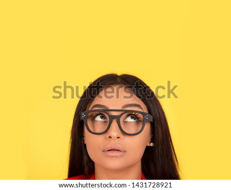 Thoughtful woman looking up. Closeup face portrait isolated on yellow background. African american caucasian indian mixed race model girl.