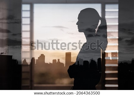 thoughtful woman looking window at the city view. Vision and future concept.