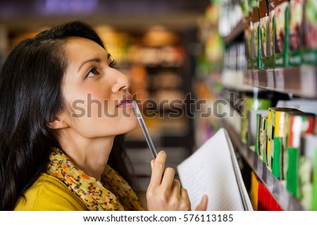 Thoughtful woman shopping for grocery in supermarket