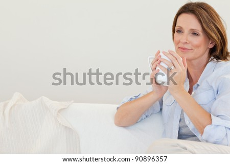 Thoughtful woman with cup of coffee on the sofa