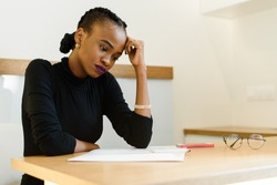 Thoughtful worried African or black American woman holding her forehead with hand looking at notepad in office