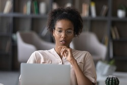 Thoughtful young African American woman in glasses look at laptop screen work online at home office. Pensive ethnic female use computer distant think ponder of problem solution. Technology concept.