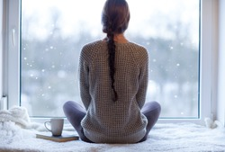 Thoughtful young brunette woman with book and cup of coffee looking through the window, blurry winter forrest landscape outside