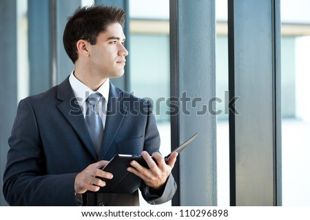 thoughtful young businessman with tablet computer