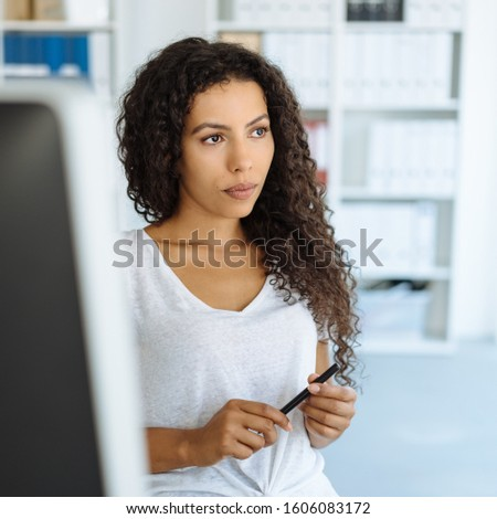 Thoughtful young businesswoman in the office sitting at her computer looking aside with a serious pensive expression