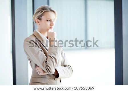 thoughtful young businesswoman looking outside of window