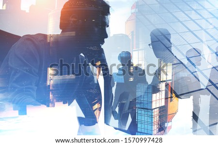 Thoughtful young CEO and blurry members of his team working together in Moscow city. Concept of leadership and collaboration. Toned image double exposure