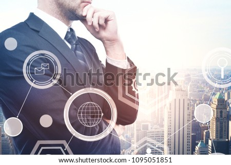 Thoughtful young european businessman standing on abstract city background with business hologram. Finance, innovation and touchscreen concept. Double exposure  #1095051851