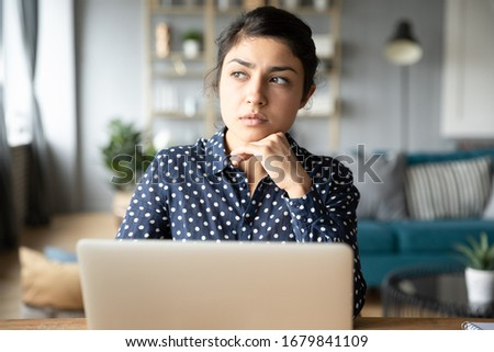 Thoughtful young Indian woman pondering task, looking to aside, working on difficult project on laptop, distracted pensive young female sitting at desk with computer, thinking about strategy