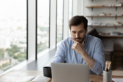Thoughtful young male employee or worker sit at desk in office work online on laptop solve business problem. Pensive businessman use computer thinking pondering over project. Planning concept.