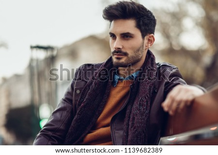 Thoughtful young man sitting on an urban bench. Attractive guy with modern hairstyle with lost look in the street.