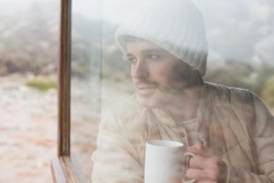 Thoughtful young man with coffee cup looking out through cabin window