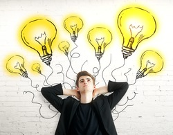 Thoughtful young man with light bulbs on brick background. Idea concept