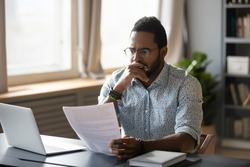Thoughtful young mixed race businessman in glasses holding paper document, reading banking debt notification. Pensive millennial african american accountant employee reviewing research report.