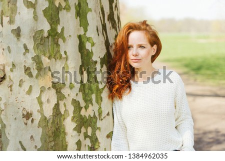 Thoughtful young redhead woman in a park standing leaning against the trunk of a large tree looking pensively to the side