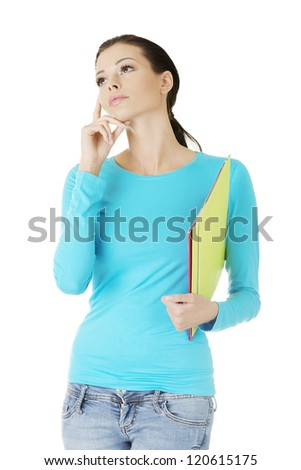 Thoughtful young student woman with notebook looking up - stock photo