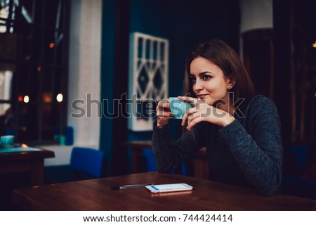 Thoughtful young woman in casual outfit drinking tasty cappuccino sitting at wooden table in stylish coffee shop interior.Contemplative hipster girl holding cup of hot beverage in handsin free time
