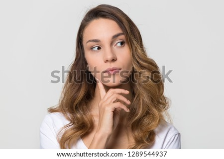 Thoughtful young woman looking away feeling doubt isolated on white studio wall, millennial girl with unsure face thinking of question considering uncertain about making decision on blank background