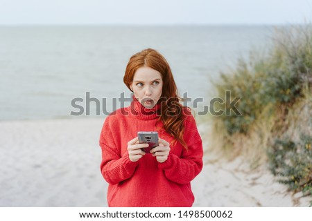 Thoughtful young woman pursing her lips in a moue as she stands holding her mobile phone on a cold misty autumn beach glancing aside with a pensive expression