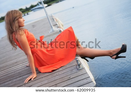 thoughtful young woman sitting on pier