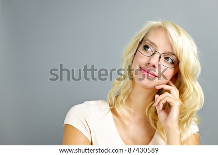 Thoughtful young woman wearing eyeglasses on grey background looking up
