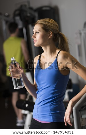Thoughtful young woman with water bottle looking away while man standing in background at gym