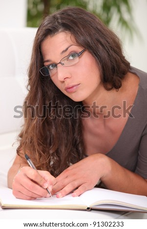 Thoughtful young woman writing in a book