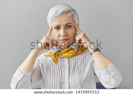 Thoughts, memory and concentration concept. Isolated image of serious concentrated mature 60 year old businesswoman holding fore fingers on her temples, trying to focus on paperwork, looking at camera #1419895553