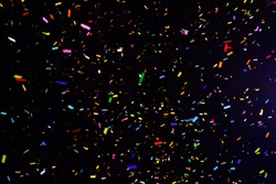 Thousands of confetti fired on air during a festival at night. Image ideal for backgrounds. Multicolor are the confetti in the picture. The sky as background is black. Multicolor tonality