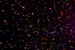 Thousands of confetti fired on air during a festival at night. Image ideal for backgrounds. Multicolor are the confetti in the picture. The sky as background is black. Warm tonality
