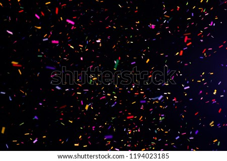 Thousands of confetti fired on air during a festival at night. Image ideal for backgrounds. Multicolor are the confetti in the picture. The sky as background is black. Hot tonality