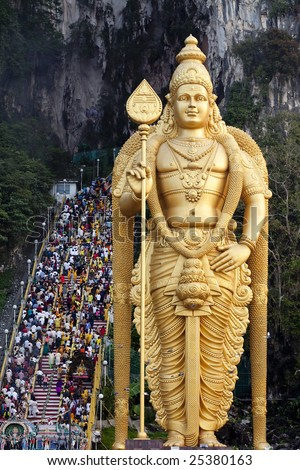 Thousands of Hindu Tamil Indians climbing steps to Batu Caves alongside statue of Lord Murugan in Kuala Lumpur, Malaysia for Thaipusam
