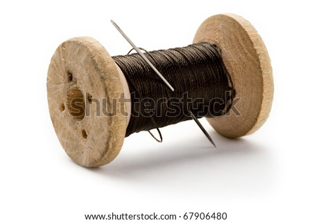 Thread bobbin and needle on white background - stock photo