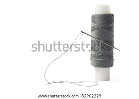 Thread bobbin and needle on white background