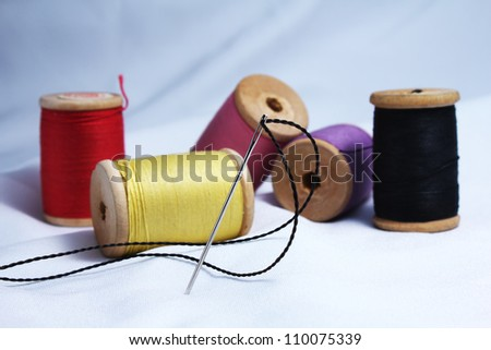 Thread bobbins and needle on fabric