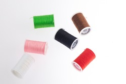 threads of different colors to mend clothes on white background.
