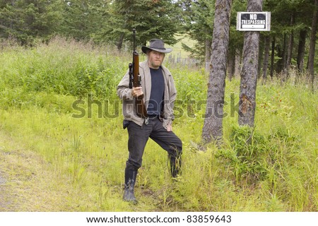 Threatening man with a gun standing by a no trespassing sign outside a country property border.