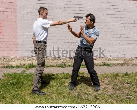 Threatening with weapons on the street. Martial arts instructors demonstrate self-defense techniques of Krav Maga