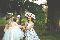 Three adorable girls in dresses hold hands in a circle