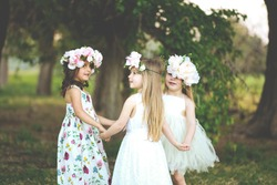 Three adorable girls in dresses hold hands in a circle holding hands