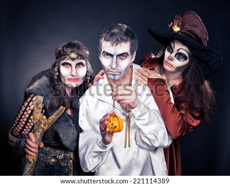 Three adults dressed in Halloween costumes.
