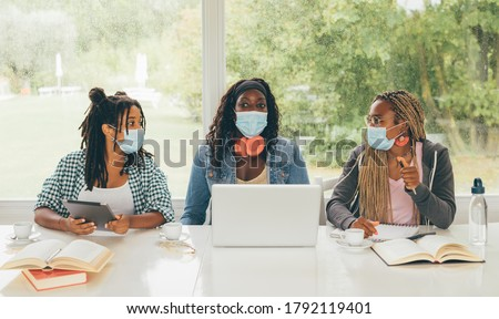 Three African American girls (students) sitting at the table studying up for test or making homework together, they are using laptop and digital tablet, wearing surgical masks. Back to school concept.