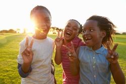 Three African elementary schoolgirls making peace signs