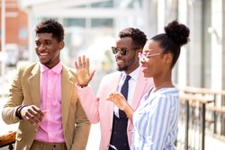 three african people are greeting their friend outdoors. hi, hello, bye. farewell concept