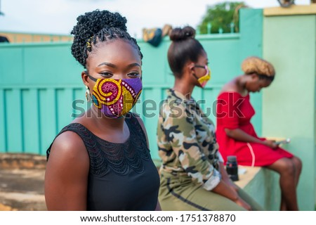 Three African women sitting apart, observing social distance - woman wearing made home made mask and looking at camera