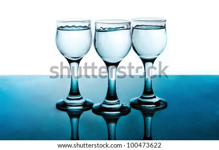 Three Alcohol Shots on glossy green surface with reflection and isolated on white background