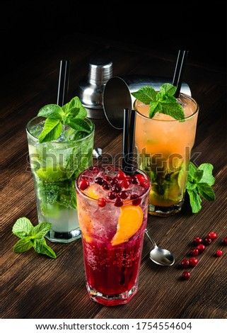 three alcoholic cocktails mojito and cranberry or lingonberry cocktail on a wooden background, refreshing mojito cocktail with ice and mint in a glass. cocktail decorated with cranberries