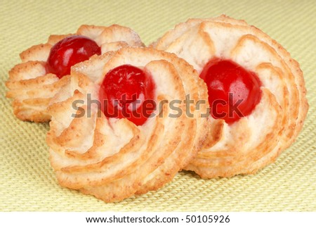 Three almond pastries decorated with red candied cherries over a light green fabric background