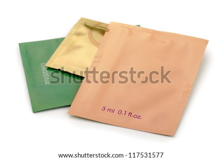 Three aluminum foil cosmetics sachets isolated on white