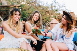 Three amazing girls in stylish vintage clothes having fun in outdoor cafe and drinking cocktails. Group of friends celebrating vacation and posing outside, holding glasses with beverage and laughing